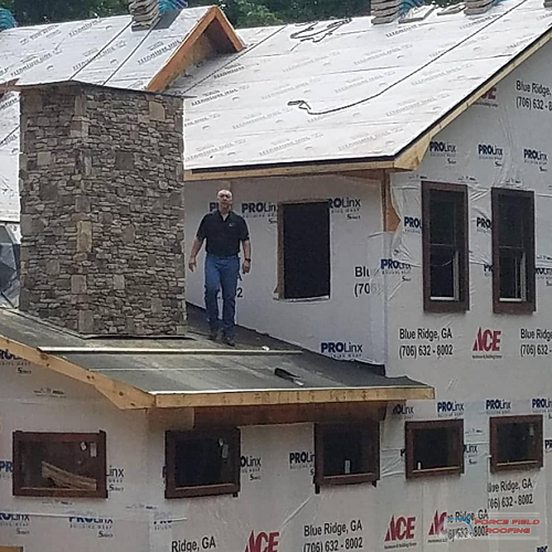 A Picture of a Force Field Roofing Roofer On a Roof.