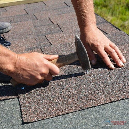 A Picture of Hands Installing New Shingles.