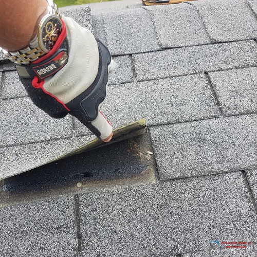 A Picture of a Finger Lifting Up a Roof Shingle.