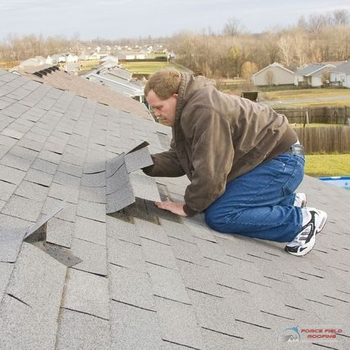A Picture of a Man Checking Uplifted Shingles After a Storm.