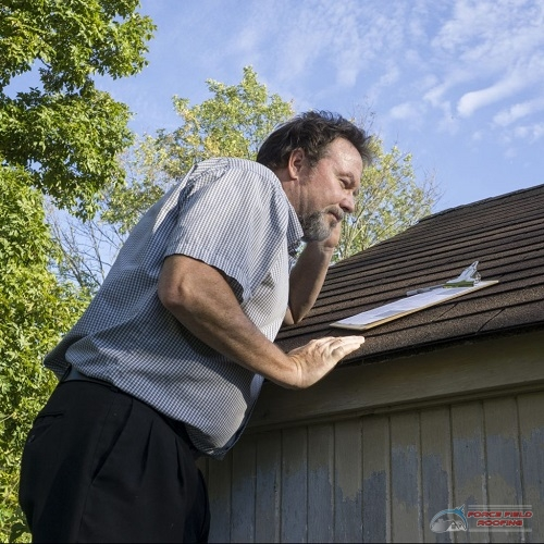 A Picture of a Man Looking at a Clipboard While Inspecting the Roof.