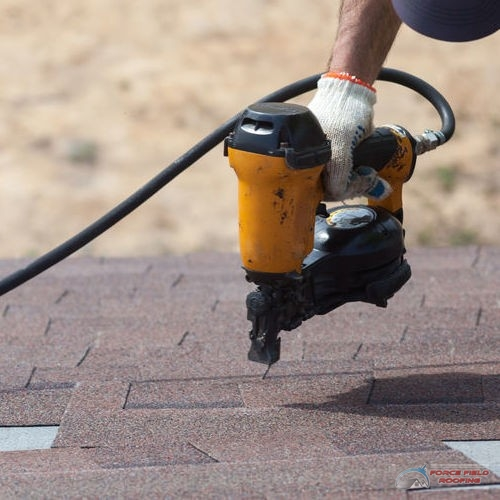 Roofer builder worker with nail gun installing Asphalt Shingles or Bitumen Tiles on a new house under construction