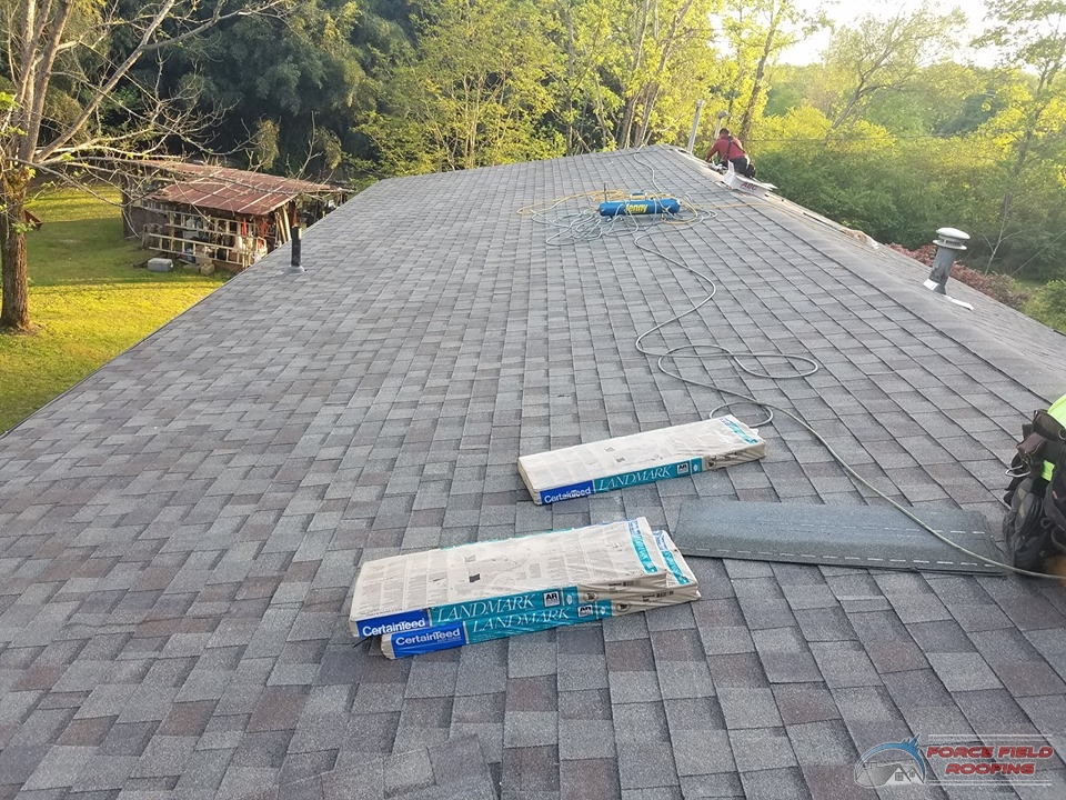 A Picture of a Roofer Repairing a Shingle Roof.