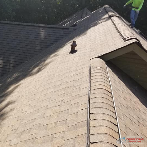A Picture of a Roofer Walking On a Shingle Roof.