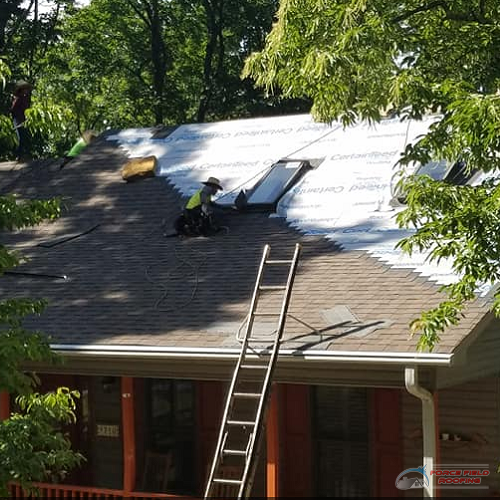 A Picture of a Roofer Working On a Shingle Roof.
