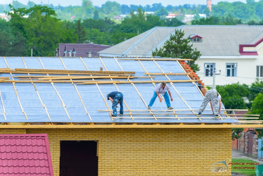 A Picture of Three Roofers Working On a Commercial Roof.